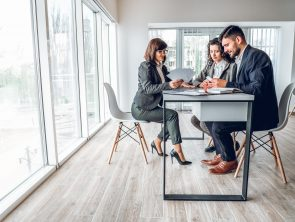 Wide angle view of group business people in bright spacious modern office near panoramic windows. Young businessman and businesswoman sitting at the desk in design studio with mature woman sales manager. Work with client concept